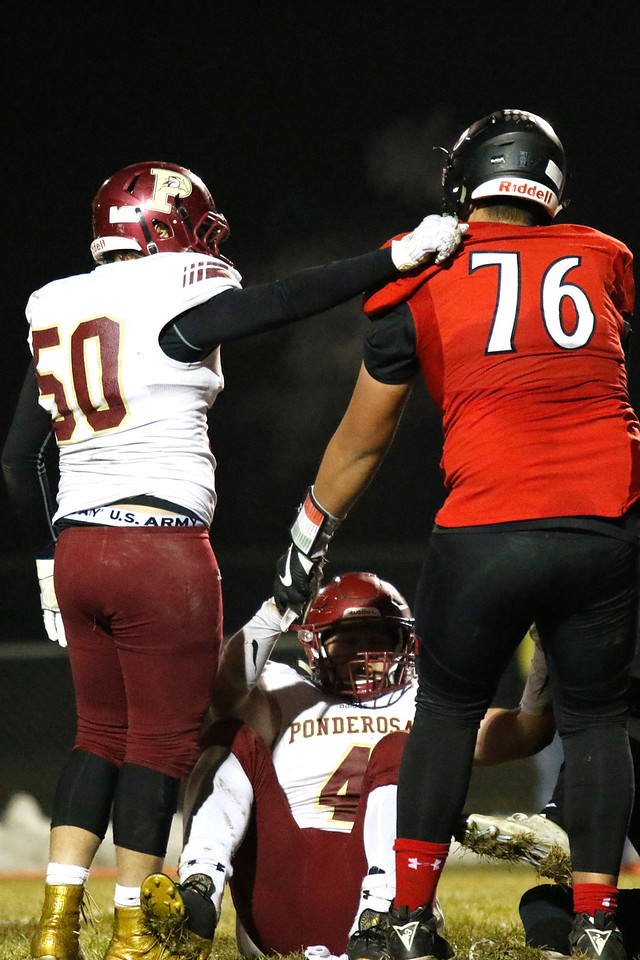 Loveland's Jayden Manu (76) helps Ponderosa's Nick Hoff (4) up as Kyle Fehtinger (50) pats him on the back  on Friday, Nov. 10, 2017, at Patterson Stadium in Loveland. (Photo by Lauren Cordova/Loveland Reporter-Herald)
