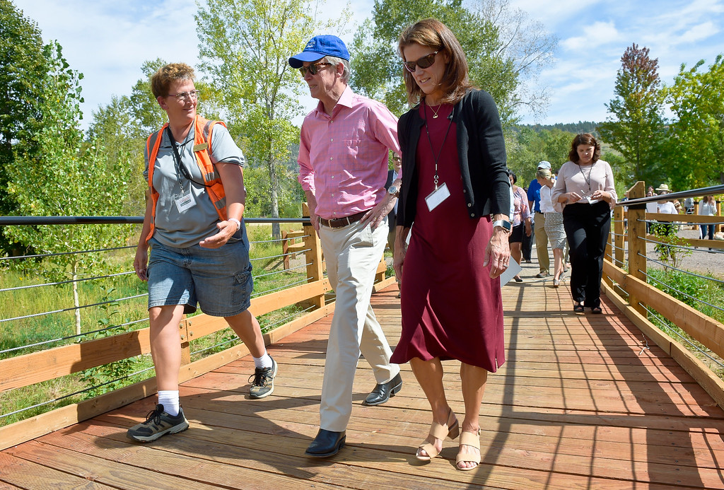 . LYONS, CO - SEPTEMBER 10, 2018: From left: Lyons employee Crystal White, Colorado governor John Hickenlooper and mayor Connie Sullivan walk across a bridge on the newly-named Hickenlooper Way in Bohn Park after the five year flood commemoration Sept. 10. The event also included a tree planting and dedication with Governor Hickenlooper and the Gerry Boland family. (Photo by Lewis Geyer/Staff Photographer)
