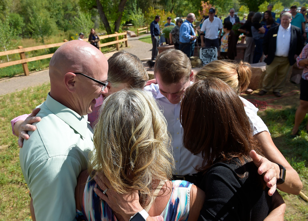 . LYONS, CO - SEPTEMBER 10, 2018: From left: Brent Boland, his sister Holli Stetson, Colorado governor John Hickenlooper, U.S. Sen. Michael Bennet, Boland\'s other sister Amy Hoh (not shown), and Lyons mayor Connie Sullivan embrace after the ceremonial tree planting during the five year flood commemoration in Bohn Park Sept. 10. Boland, Stetson, and Hoh are the children of Gerry Boland, a Lyons resident who died in the flood. (Photo by Lewis Geyer/Staff Photographer)