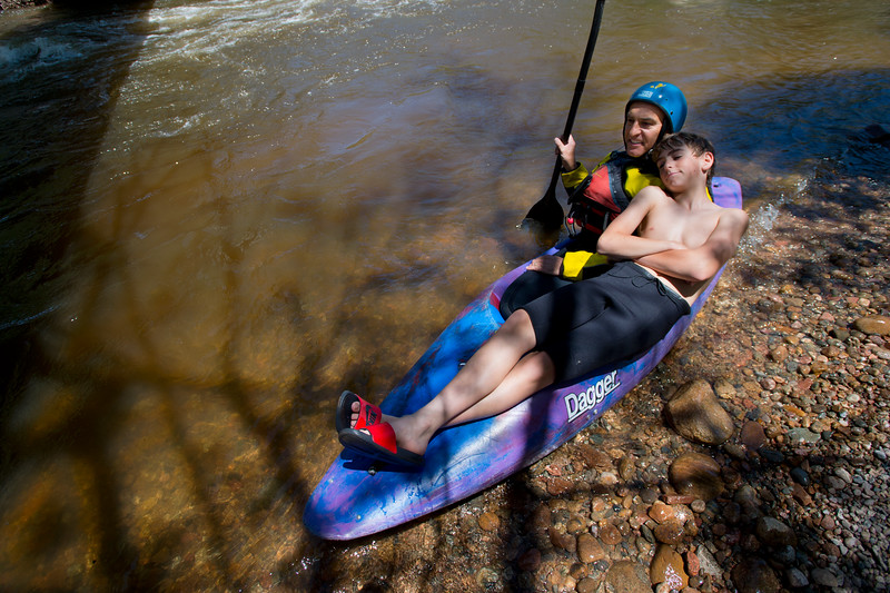 "Nick Sutcliffe (left) sits with his son Charlie Sutcliffe, 14, on his kayak as they watch the kayak slalom competition as part of the Lyons Outdoor Games at Black Bear Hole in Bohn Park on Saturday. <br /> More photos:  <a href=""http://www.dailycamera.com"">http://www.dailycamera.com</a><br /> (Autumn Parry/Staff Photographer)<br /> June 4, 2016"