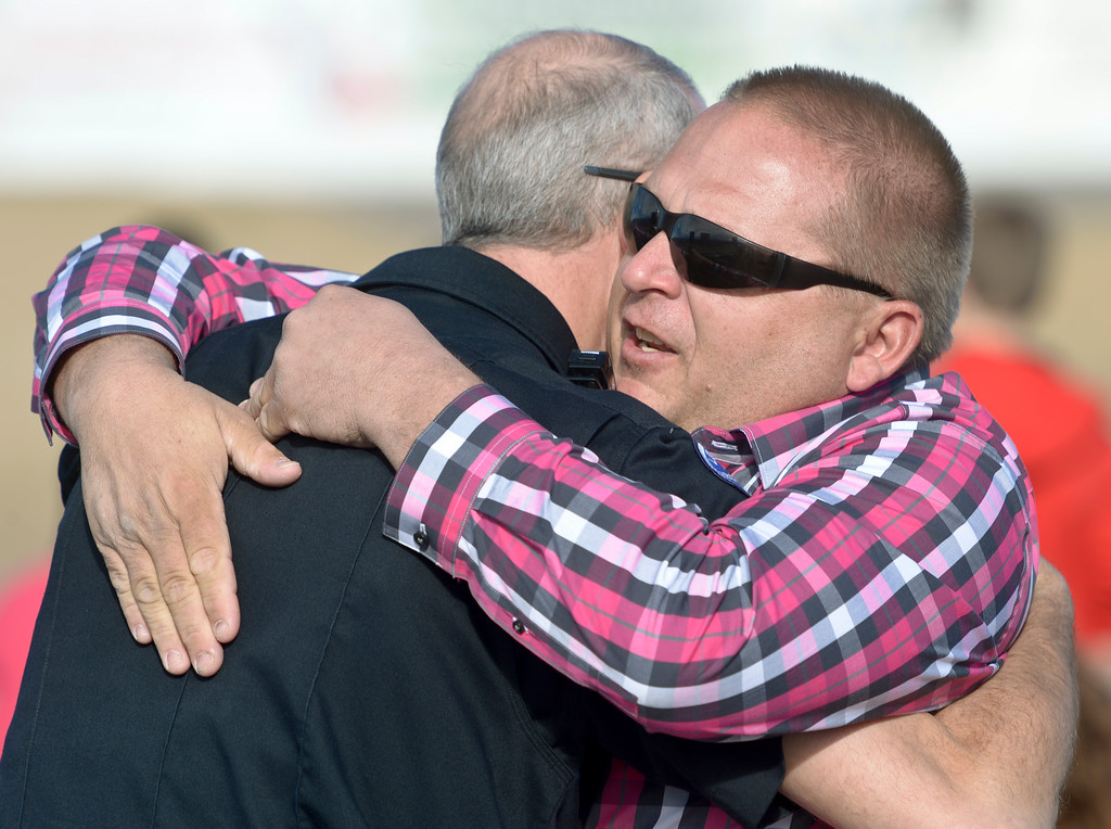 . Makayla Grote\'s father Troy Grote, right, is embraced by Longmont Police sergeant Bruce Pettitt before the start of Makayla\'s memorial service at Colorado National Speedway Sunday afternoon. To view more photos and a video visit timescall.com. Lewis Geyer/Staff Photographer Nov. 26, 2017
