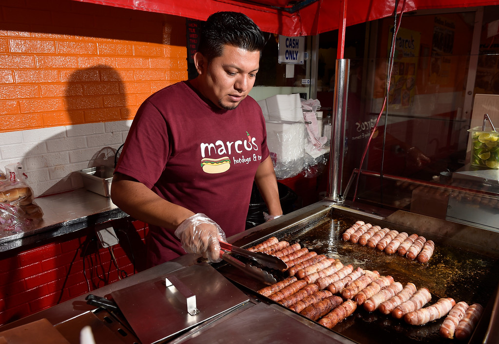 . LONGMONT, CO - AUG. 7: Arturo Silva grills bacon-wrapped hot dogs at Marcos Hot Dogs and Tacos, 1647 Kimbark St. Aug. 7. The food stand opened 18 years ago.  (Photo by Lewis Geyer/Staff Photographer)
