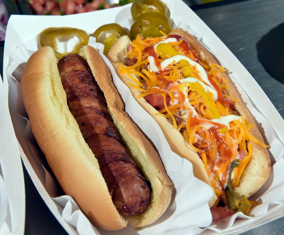 . LONGMONT, CO - AUG. 7: A plain bacon-wrapped hotdog and the Fully Loaded hot dog at Marcos Hot Dogs and Tacos, 1647 Kimbark St. Aug. 7. The Fully Loaded is topped with pinto beans, mayonnaise, tomato, ketchup, mustard, onion and cheese. (Photo by Lewis Geyer/Staff Photographer)