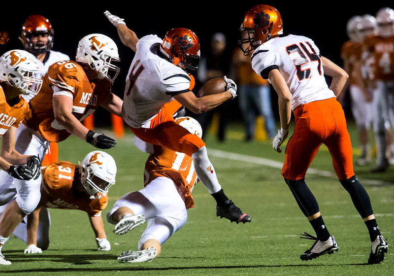 "Erie's Noah Roper leaps over Mead's Ryan Lavanchy before he is tackled by Mead's defense during the game at Mead High School on Friday. <br /> More photos:  <a href=""http://www.BoCoPreps.com"">http://www.BoCoPreps.com</a><br /> (Autumn Parry/Staff Photographer)<br /> October 28, 2016"