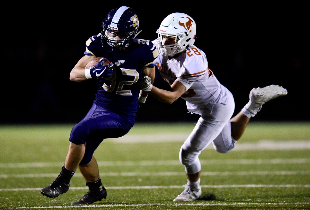 . Frederick High School\'s Jacob Cole (No. 32) is shoved out of bounds by Mead High School\'s Evan Hansen (No. 28) in Frederick, Colorado on Oct. 12, 2017. (Photo by Matthew Jonas/Times-Call)