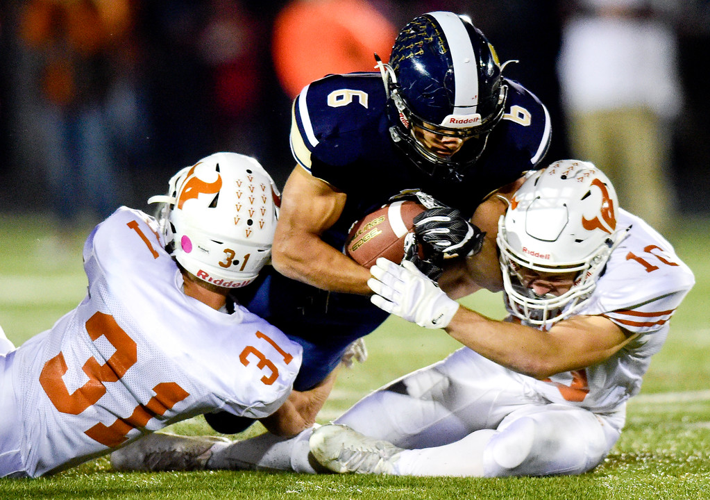 . Mead High School\'s Trace Lindemann (No. 31) and Ryan LaVanchy (No. 10) bring down Frederick High School\'s James Jones (No. 6) in Frederick, Colorado on Oct. 12, 2017. (Photo by Matthew Jonas/Times-Call)