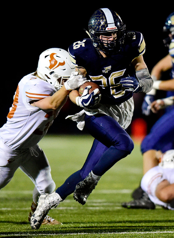 . Frederick High School\'s Matt Olson (No. 26) tries to shake a tackle from Mead High School\'s Greyson Young (No. 38) in Frederick, Colorado on Oct. 12, 2017. (Photo by Matthew Jonas/Times-Call)