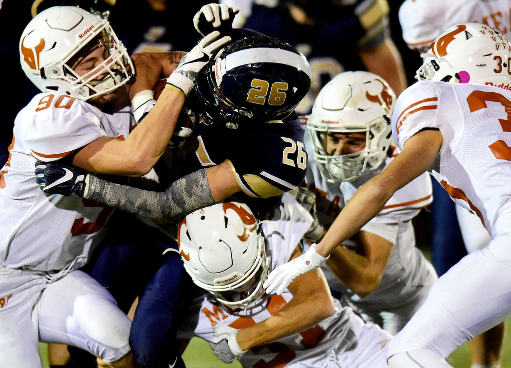 . Frederick High School\'s Matt Olson (No. 26) is wrapped up by Mead High School defense in Frederick, Colorado on Oct. 12, 2017. (Photo by Matthew Jonas/Times-Call)