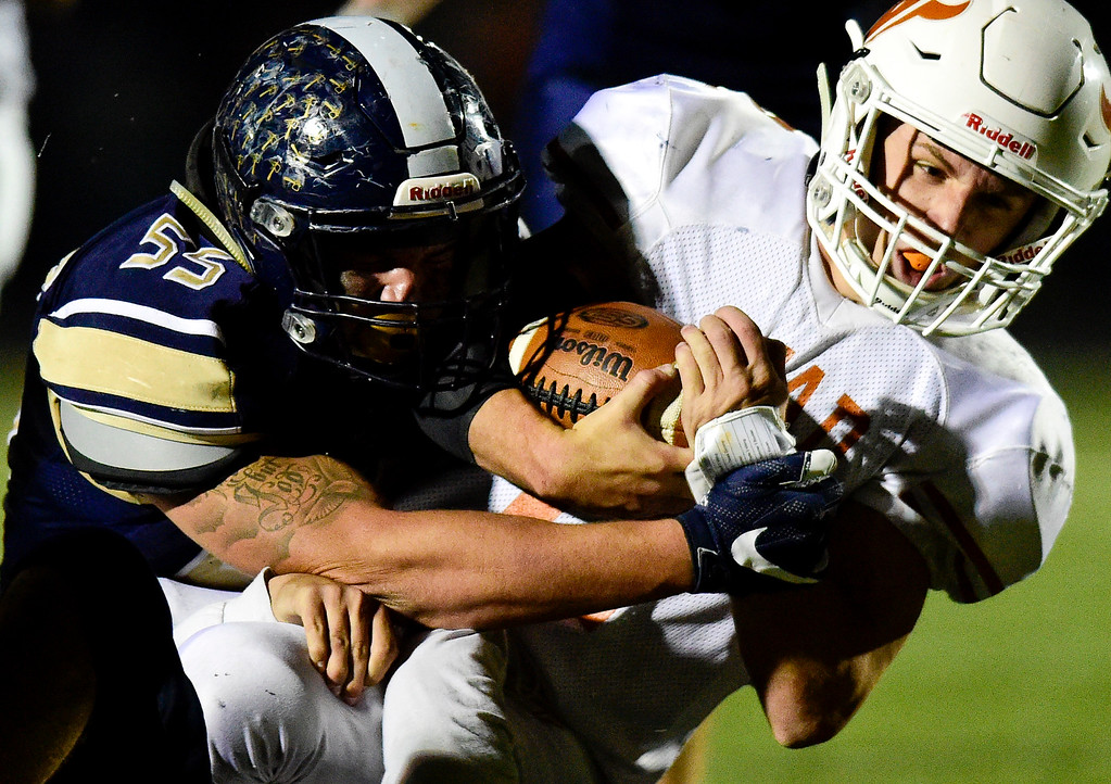 . Mead High School\'s Tyler Keys (No. 2) is brought down by Frederick High School\'s Matt Johnson (No. 55) in Frederick, Colorado on Oct. 12, 2017. (Photo by Matthew Jonas/Times-Call)