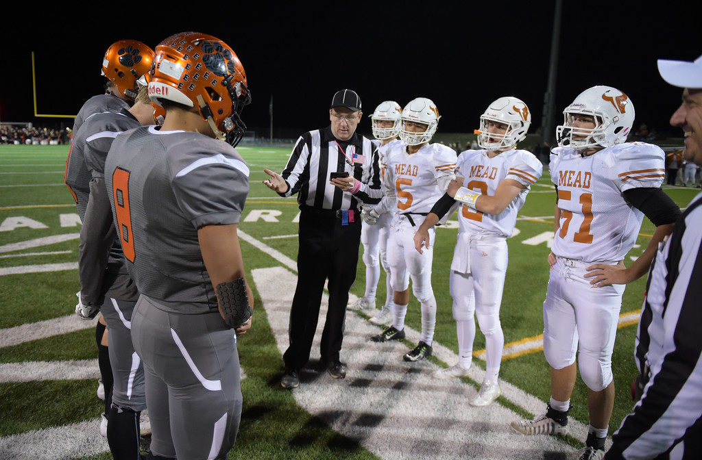 . The Erie and Mead captains meet on the field for the coin toss Friday night at Erie High School. To view more photos visit bocopreps.com. Lewis Geyer/Staff Photographer Oct. 24, 62017