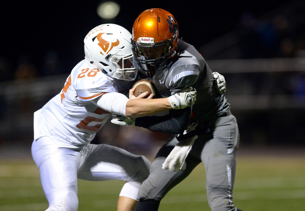 . Mead\'s Nathan Mackey wraps up Erie\'s Jacob Mansdorfer in the fourth quarter Friday night at Erie High School. Mead won 42-28. To view more photos visit bocopreps.com. Lewis Geyer/Staff Photographer Oct. 24, 62017