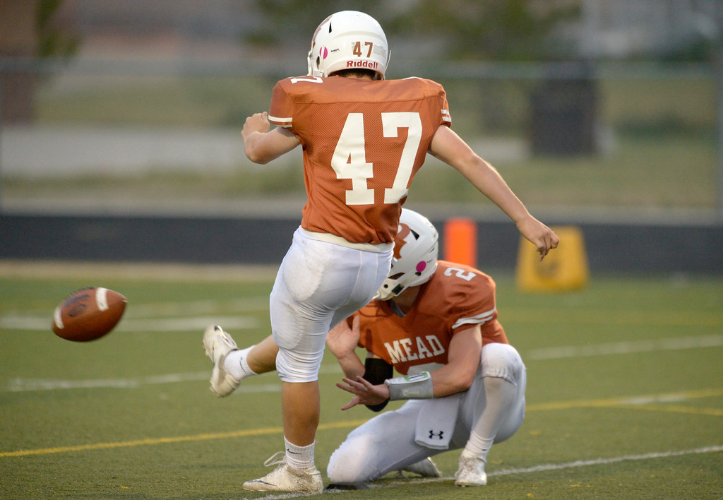 . With the help of Tyler Keys, Mead\'s Taylor Kamigaki kicks an extra point against Vista PEAK Prep in the first quarter Friday night at Mead High School. To view more photos visit bocopreps.com. Lewis Geyer/Staff Photographer Sept. 08, 2017