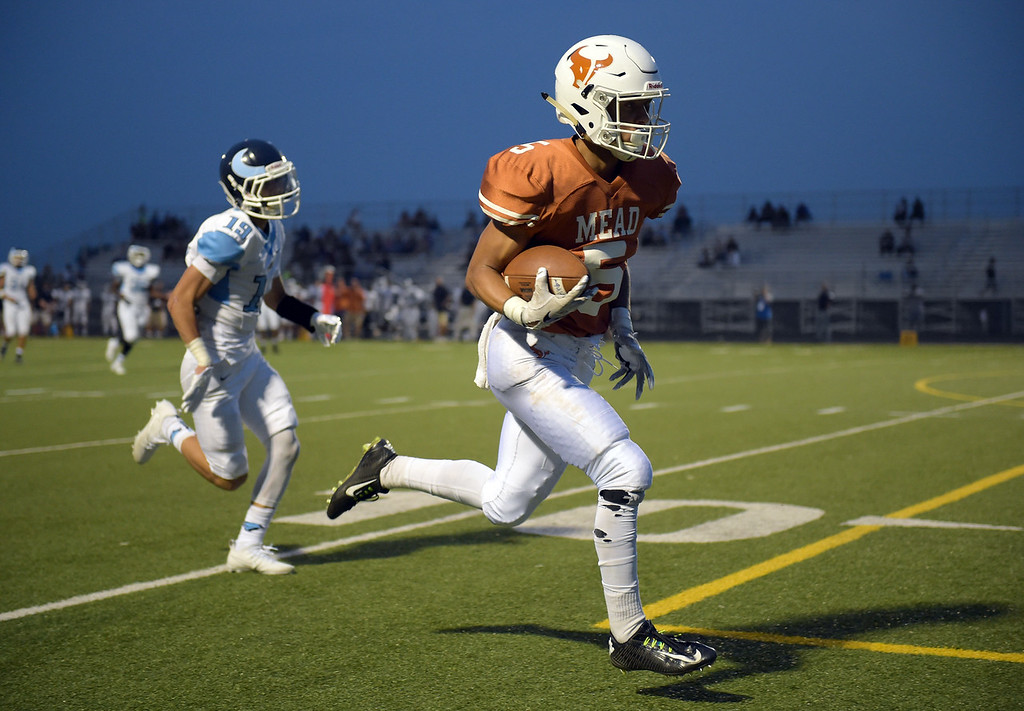 . Mead\'s Dominic Esters stays in front of Vista PEAK Prep\'s Kai Bocalbos to score a touchdown in the second quarter Friday night at Mead High School. To view more photos visit bocopreps.com. Lewis Geyer/Staff Photographer Sept. 08, 2017