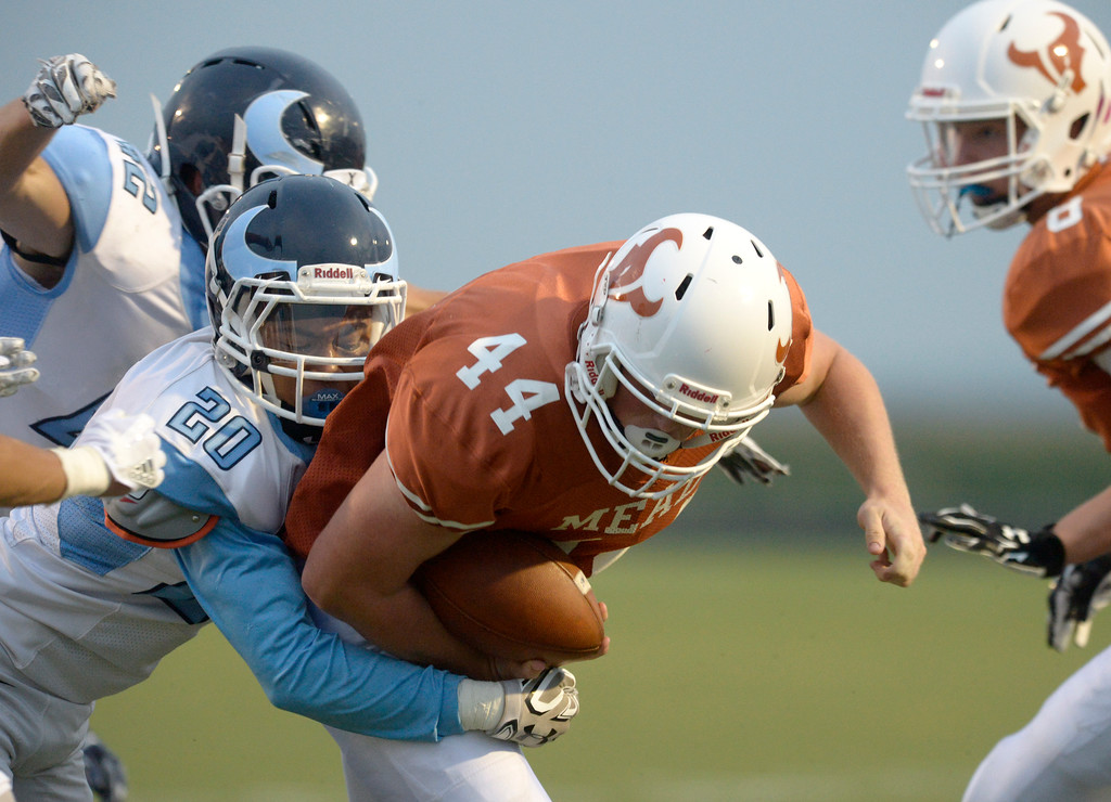 . Mead\'s Derek Edwards is tackled by Vista PEAK Prep\'s Jaden Tolbert in the first quarter Friday night at Mead High School. To view more photos visit bocopreps.com. Lewis Geyer/Staff Photographer Sept. 08, 2017