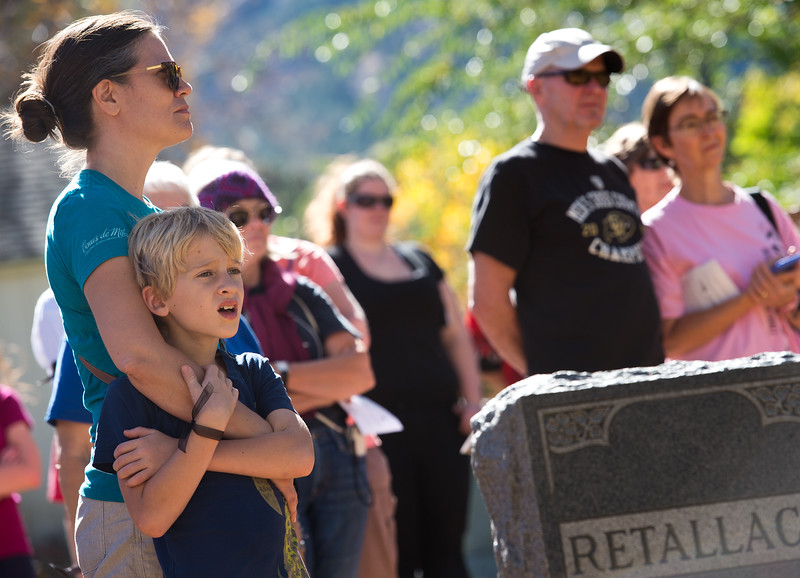 """Kim Popetz stands with her son Max Popetz, 8, as they watch the Buffalo Soldiers of the American West pay tribute to Edward Baker, a fallen buffalo soldier, during Meet the Spirits at Columbia Cemetery in Boulder on Sunday. <br /> More photos:  <a href=""""http://www.dailycamera.com"""">http://www.dailycamera.com</a><br /> (Autumn Parry/Staff Photographer)<br /> October 16, 2016"""