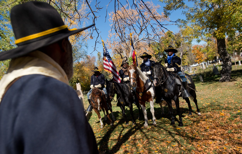 """From left to right, Buffalo Soldiers of the American West Gary Moore, Ken Johnson, Kenny Wyatt and Tony Johnson pay tribute to Edward Baker, a fallen buffalo soldier, during Meet the Spirits at Columbia Cemetery in Boulder on Sunday. <br /> More photos:  <a href=""""http://www.dailycamera.com"""">http://www.dailycamera.com</a><br /> (Autumn Parry/Staff Photographer)<br /> October 16, 2016"""