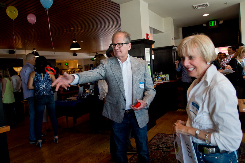"""Michael Hagerty participates in a wine ring toss, as his wife, Julie Alderman-Hagerty, who is also a teacher at Mesa Elementary, watches during Mesa Elementary's """"Denim and Bling"""" Spring Fling fundraiser at Under the Sun in Boulder.<br /> More photos:  <a href=""""http://www.dailycamera.com"""">http://www.dailycamera.com</a><br /> Autumn Parry/Staff Photographer<br /> April 24, 2016"""