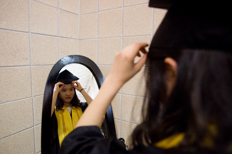 "Hye Min Kim adjusts her cap in a mirror prior to the commencement ceremony for Monarch High School at 1stBank Center in Broomfield on Friday.<br /> More photos:  <a href=""http://www.dailycamera.com"">http://www.dailycamera.com</a><br /> Autumn Parry/Staff Photographer<br /> May 20, 2016"