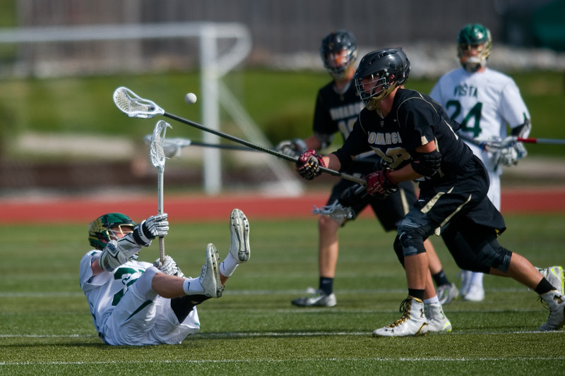 "Mountain Vista's Jack McFarlane passes the ball to a teammate as he falls before Monarch's Derek Coleman during the 5A lacrosse quarterfinals against Mountain Vista at Legacy Stadium in Aurora on Saturday. Mountain Vista defeated Monarch 15-9.<br /> More photos:  <a href=""http://www.BoCoPreps.com"">http://www.BoCoPreps.com</a><br /> Autumn Parry/Staff Photographer<br /> May 14, 2016"