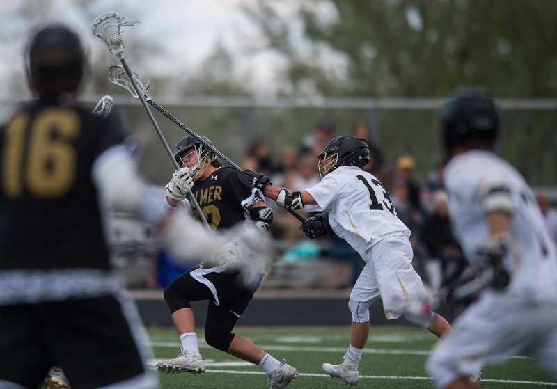 "Monarch's Danny Kowalski  tries to knock the ball away from Palmer's Isaac Atencio during the game at Monarch High School on Wednesday. Monarch defeated Palmer 13-9.<br /> More photos:  <a href=""http://www.BoCoPreps.com"">http://www.BoCoPreps.com</a><br /> Autumn Parry/Staff Photographer<br /> May 11, 2016"