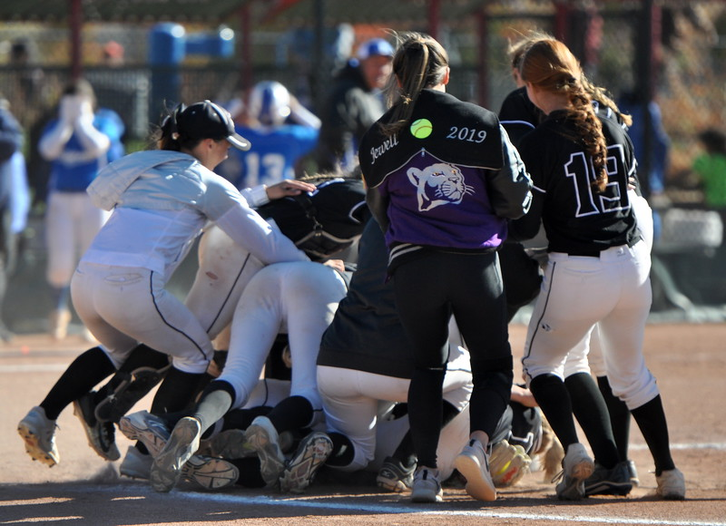 Mountain View players dogpile pitcher Bailey Carlson in the circle Saturday in Aurora after winning the state championship. (Cris Tiller / Loveland Reporter-Herald)