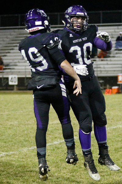 Mountain View's Wes Evangelista (30) celebrates with Chad Baumann (19) after bringing the ball back to their team on Friday, Oct. 27, 2017, at Patterson Stadium in Loveland. (Photo by Lauren Cordova/Loveland Reporter-Herald)