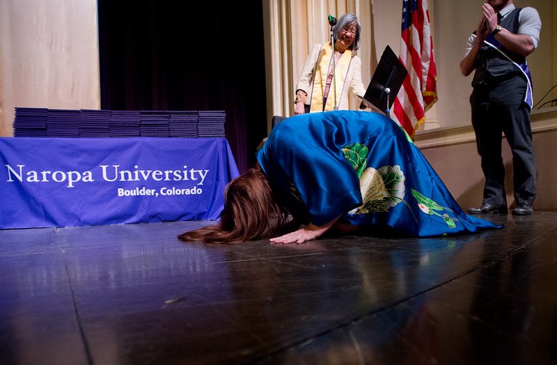 "Stella Bonnie performs prostrations on the stage before accepting her diploma at Naropa University's commencement ceremony in Macky Auditorium on Sunday. <br /> More photos:  <a href=""http://www.dailycamera.com"">http://www.dailycamera.com</a><br /> Autumn Parry/Staff Photographer<br /> May 8, 2016"