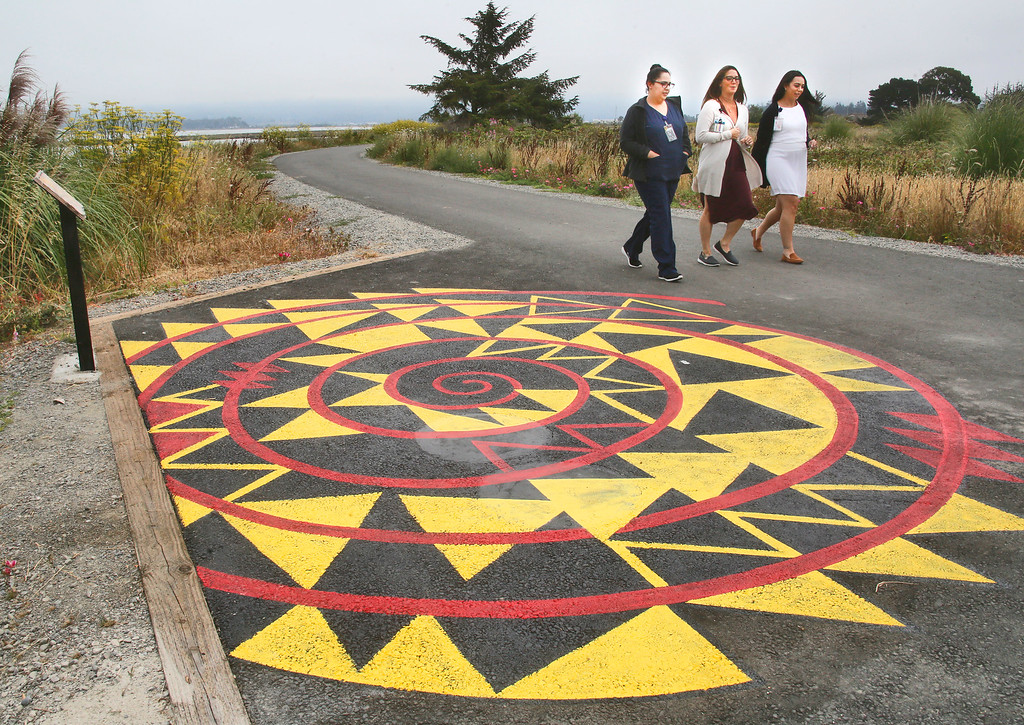 . Shaun Walker � The Times-Standard  Vira Nuñez, left, Malia Honda, and Ashley Chiu, all of Eureka Community Health and Wellness Center, walk Tuesday next to new Eureka Waterfront Trail art created by Karuk-Yurok artist Alme Allen and several friends. That area next to the trail northwest of Blue Ox Millworks will be dedicated to Wiyot life and culture and will soon have concrete versions of traditional native stools. The painted design is from a section of the Indian Island themed mural at Morris Graves Museum, �The Sun Set Twice On The People That Day�, that Allen and Brian Tripp painted in 2000 and partly represents salmon spawning and generations of life.