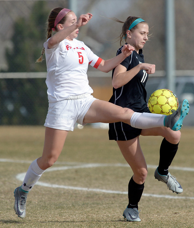 . Skyline\'s Kalen Niedling kicks the ball next to Niwot\'s Roxie Pasma in the first half Tuesday at Skyline High School. Lewis Geyer/Staff Photographer March 21, 2017