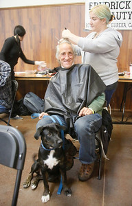 Veteran Glenn Simcox of Eureka  gets a haircut from Deven Thompson, a Frederick and Charles Beauty College student, as his dog Katy sits next to him at the North Coast Stand Down at the Humboldt County Fairgrounds in Ferndale on Friday. The annual three-day event provides a variety of services to all veterans and their families. It continues today from 9 a.m. to 6 p.m. and Sunday from 9 a.m. to noon. For more information, go to northcoaststanddown.org. (Shaun Walker -- The Times-Standard)