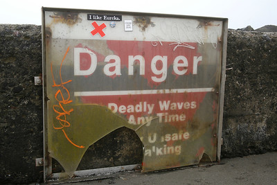 A vandalized and deteriorated sign sits near the base of the North Jetty outcrop itself on Thursday, where the waves it warns about help damage it. Two similar signs in better condition sit in the sand dunes near the main parking lot. (Shaun Walker -- The Times-Standard)