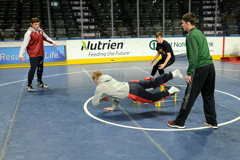 Berthoud's Austyn Binkly dives to make a shot as teammate Brock Johnson (far left) looks on as they play Spikeball against wrestlers from Casper Kelly Walsh prior to Friday's start of the Northern Colorado Christmas Tournament at the Budweiser Events Center. (Mike Brohard/Loveland Reporter-Herald)