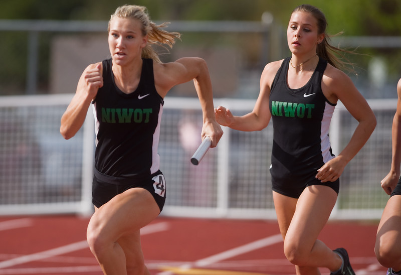 "Niwot's Ashley Herring (right) hands off the baton to Kela Fetters during the girls 100 meter relay during the Northern/Tri-Valley/Mile High League Championships at Longmont High School on Friday.<br /> More photos:  <a href=""http://www.BoCoPreps.com"">http://www.BoCoPreps.com</a><br /> Autumn Parry/Staff Photographer<br /> May 6, 2016"