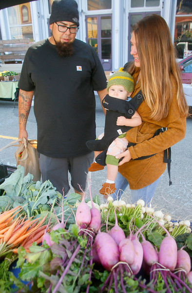 Shaun Walker — The Times-Standard  Laila Barnett, 8 months, mom Hannah, and dad Jeff look at produce at the I and I Farm tables at the Old Town Eureka Farmers Market on Tuesday morning. The market, on F Street between 1st and 2nd, is open every Tuesday from 10 a.m. to 1 p.m. June through October. For more information on it and other farmers markets, go to www.northcoastgrowersassociation.org.