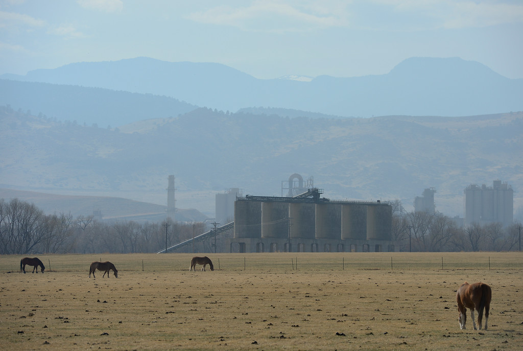 . Horses are seen grazing in a pasture near Colo. 66 and 63rd Street on Wednesday. Storage silos on a property owned by Martin Marietta Materials can be seen behind the pasture. On Jan. 3, Boulder County commissioners approved a plan for constructing a processing plant and other structures on the property. More photos: DailyCamera.com. Matthew Jonas/Staff Photographer March 22,  2017