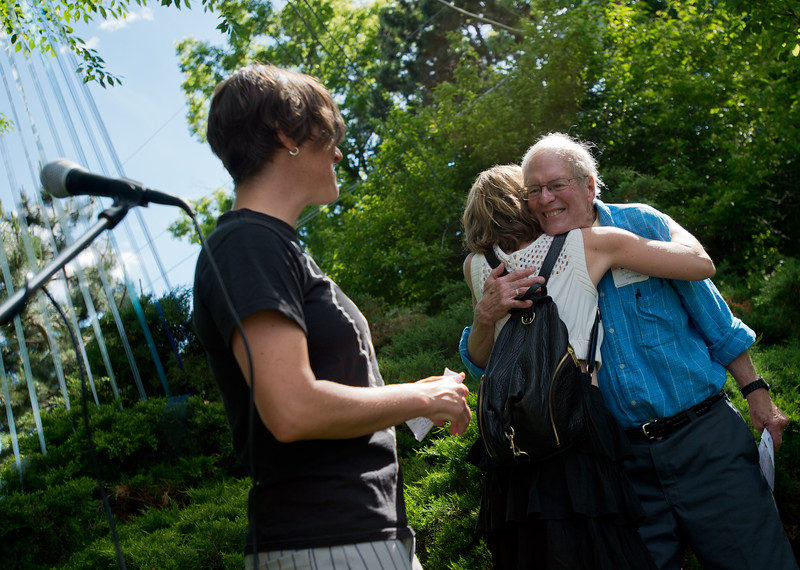 """Bethy Leonardi, left, watches as Sara Staley hugs John Hoffman as they present him with the """"Jack and Jean Hodges Big Hearts Award"""" during Out Boulder's Garden Party on Sunday.<br /> More photos:  <a href=""""http://www.dailycamera.com"""">http://www.dailycamera.com</a><br /> (Autumn Parry/Staff Photographer)<br /> June 5, 2016"""