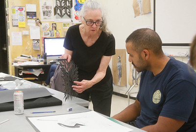 Ann Chadwick Reid of Bow, Washington, discusses paper cut art ideas with Miles Alexander of Arcata during her visiting artist workshop at College of the Redwoods on Wednesday. She shared her process of making a paper cut using stencils to design a layout and cutting techniques to achieve the desired results. (Shaun Walker — The Times-Standard)
