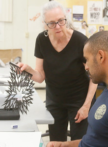 Ann Chadwick Reid of Bow, Washington, discusses and helps with paper cut art ideas during her visiting artist workshop at College of the Redwoods on Wednesday. She shared her process of making a paper cut using stencils to design a layout and cutting techniques to achieve the desired results. (Shaun Walker — The Times-Standard)