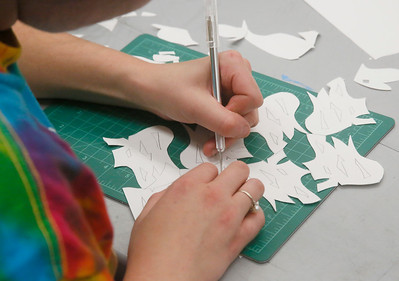A student uses a hobby knife to cut stencils for making her design. (Shaun Walker -- The Times-Standard)