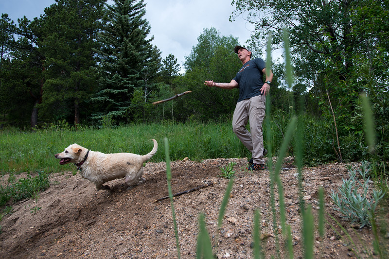 "Pastor Jim Burgen tosses a stick into a pond for his dog, Gertie, near his home in Allenspark on Friday, July 1, 2016.<br /> More photos:  <a href=""http://www.dailycamera.com"">http://www.dailycamera.com</a><br /> (Autumn Parry/Staff Photographer)<br /> July 1, 2016"