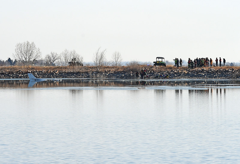 Rescue personnel stand on the shore of Culver Reservoir Monday morning, Feb. 27, 2017, after a plane crashed into the lake southwest of Berthoud. Divers from Berthoud Fire, Loveland Fire Rescue Authority and Larimer County Diver Rescue, worked on scene trying to get the plane closer to shore. Two males who were pulled from the plane were prononced dead. (photo by Jenny Sparks/Loveland Reporter-Herald)