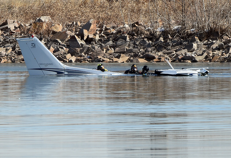 Divers work to attach a floatation device to an airplane Monday morning, Feb. 27, 2017, that crashed into Culver Reservoir southwest of Berthoud. Divers from Berthoud Fire, Loveland Fire Rescue Authority and Larimer County Diver Rescue, worked on scene trying to get the plane closer to shore. Two males who were pulled from the plane were prononced dead. (photo by Jenny Sparks/Loveland Reporter-Herald)