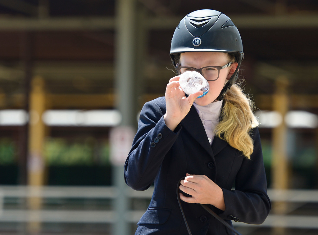 . Olivia Frankenfield, 11, of Oklahoma, tries to keep cool in the hot sun during the 2018 Rocky Mountain Regional and West World Pony of the Americas horse show Sunday at the Boulder County Fairgrounds. To view more photos visit timescall.com. Lewis Geyer/Staff Photographer July 08, 2018