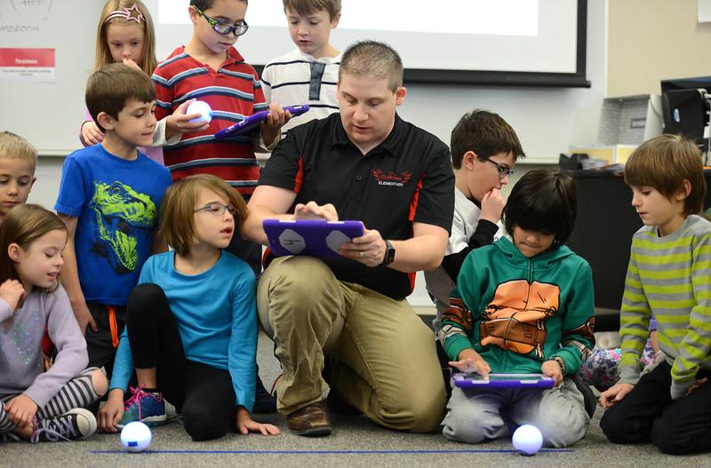 Computer science teacher Chris Schmitz helps second graders set up iPads to program Sphero robotic balls Monday morning at Red Hawk Elementary in Erie. (Staff Photographer Lewis Geyer) Jan. 11, 2016