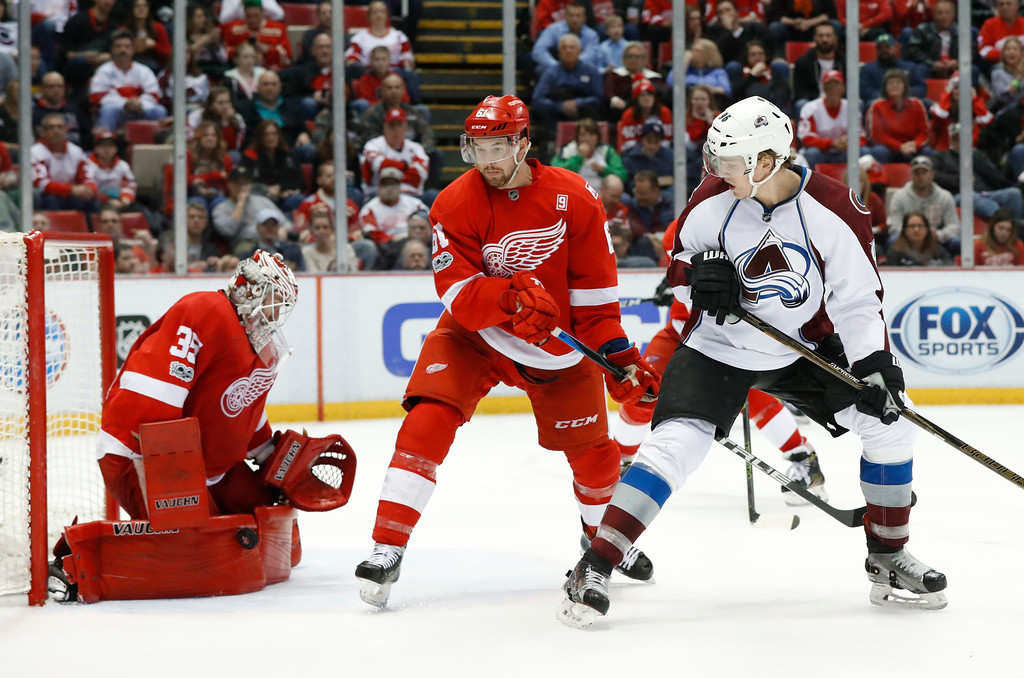. Detroit Red Wings goalie Jimmy Howard (35) stops a shot as Colorado Avalanche right wing Mikko Rantanen, right, watches with Xavier Ouellet (61)in the third period of an NHL hockey game Saturday, March 18, 2017, in Detroit. (AP Photo/Paul Sancya)