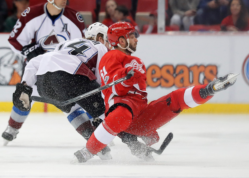 . Colorado Avalanche defenseman Anton Lindholm (54) checks Detroit Red Wings center Frans Nielsen (51) in the first period of an NHL hockey game Saturday, March 18, 2017, in Detroit. (AP Photo/Paul Sancya)