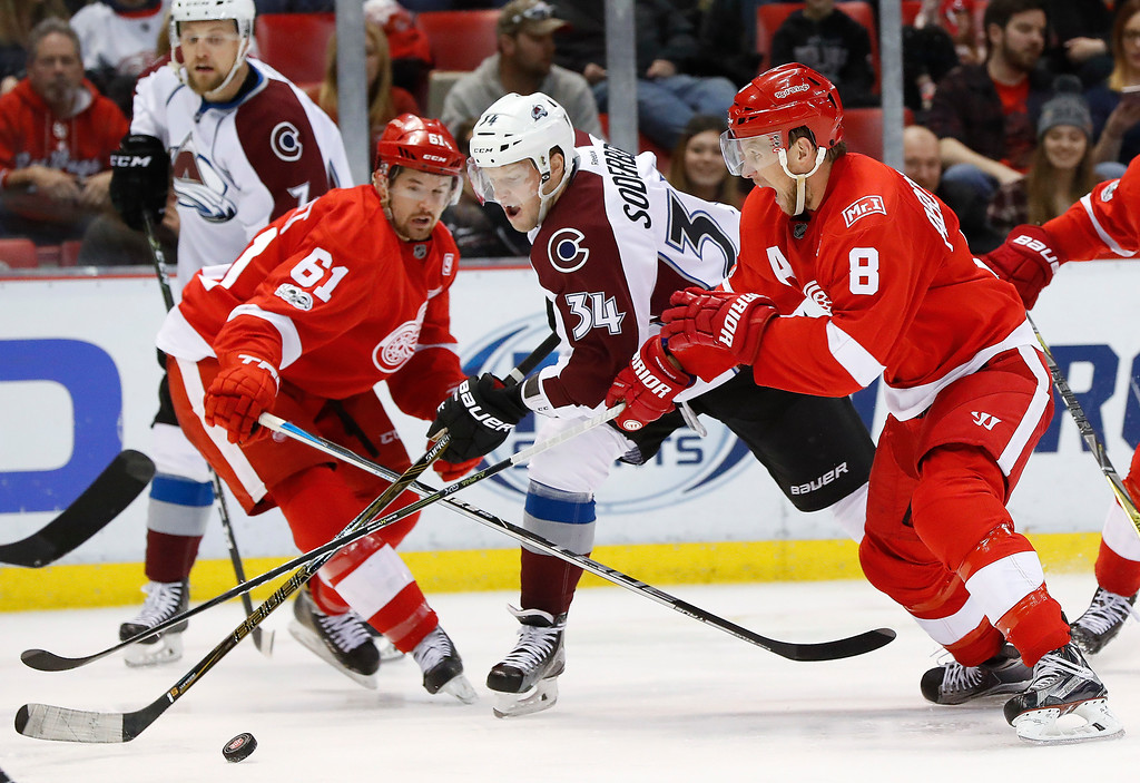 . Colorado Avalanche center Carl Soderberg (34) is defended by Detroit Red Wings defenseman Xavier Ouellet (61) and Justin Abdelkader (8) in the third period of an NHL hockey game Saturday, March 18, 2017, in Detroit. (AP Photo/Paul Sancya)