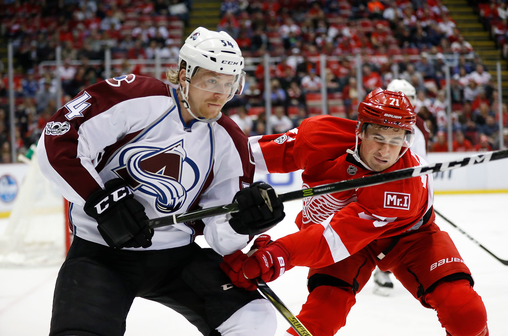 . Colorado Avalanche defenseman Anton Lindholm (54) and Detroit Red Wings center Dylan Larkin (71) battle for position in the second period of an NHL hockey game Saturday, March 18, 2017, in Detroit. (AP Photo/Paul Sancya)