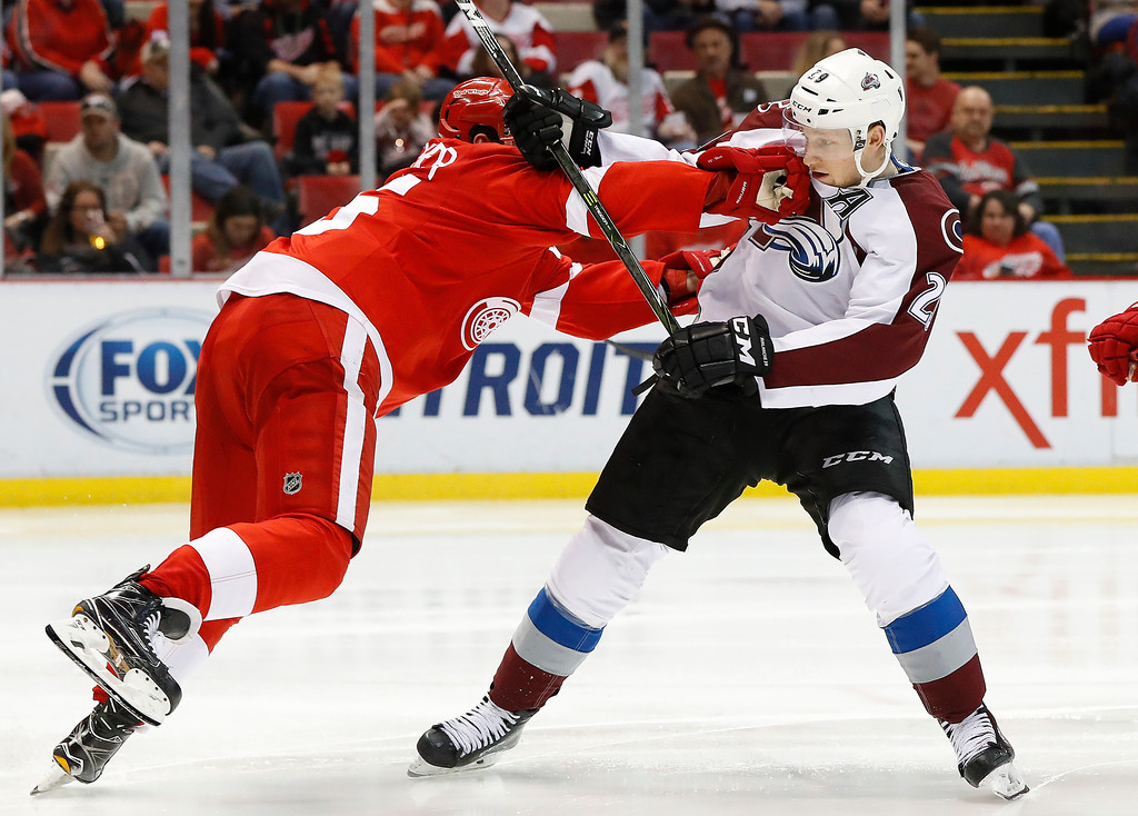 . Detroit Red Wings defenseman Danny DeKeyser (65) defends Colorado Avalanche center Nathan MacKinnon (29) in the third period of an NHL hockey game Saturday, March 18, 2017, in Detroit. (AP Photo/Paul Sancya)