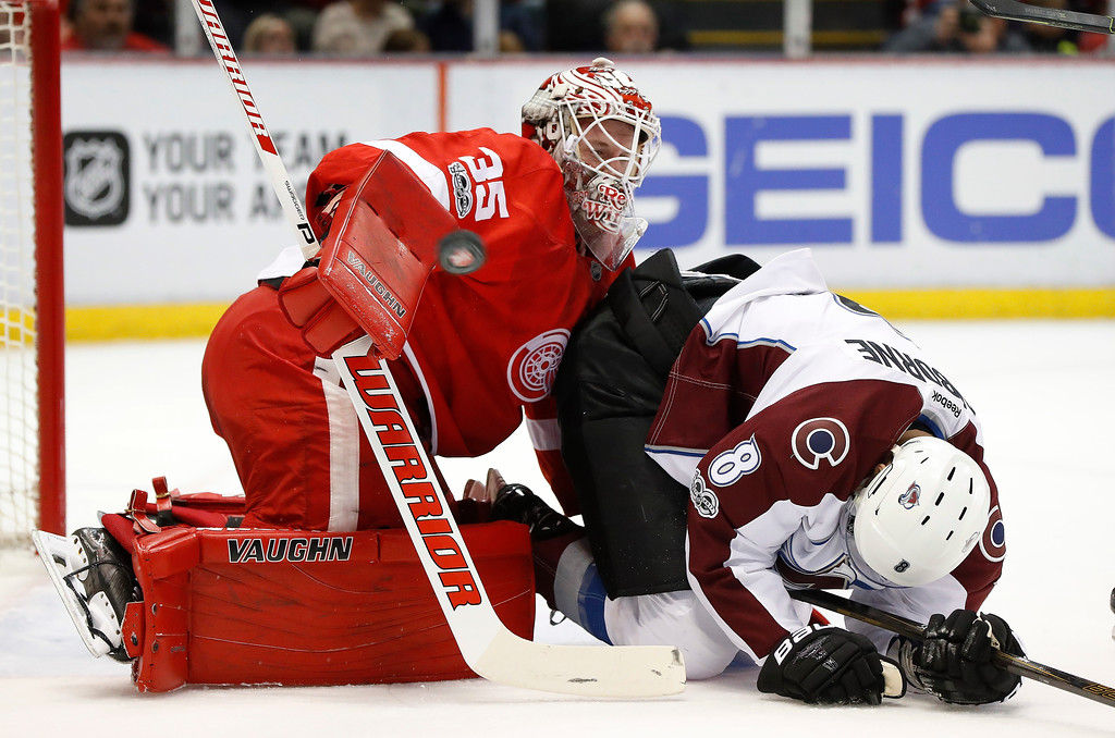 . Detroit Red Wings goalie Jimmy Howard (35) stops a shot as Colorado Avalanche center Joe Colborne (8) falls in the first period of an NHL hockey game Saturday, March 18, 2017, in Detroit. (AP Photo/Paul Sancya)